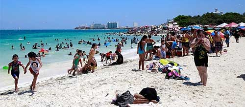 Visitors enjoy the beach in Cancun, Mexico, in April 2015. Photograph: Cassi Alexandra/Bloomberg/Getty Images