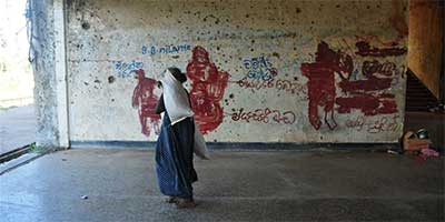 A woman walks past a wall at the former railway station in Northern Jaffna, splattered with bullet holes and graffiti left by southern tourists | Photo: Amantha Perera/IRIN