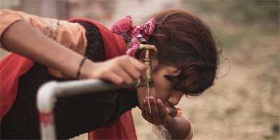 A girl drinks directly from a public tap in Nawalparasi installed last year, promising arsenic-free water to users; education for proper use and maintenance of arsenic mitigation technologies remains a challenge for government and stakeholders | Photo: Marcus Benigno/IRIN