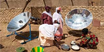 Women prepare food using a solar cooker in Mali. Photo: Joerg Boethling | Alamy