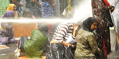 Maldivian women brave water cannon at a protest rally. | Photo: IPS