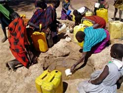 Ugandan women and children collect water from a hole dug in a dry riverbed at Kaabong village, Karamoja region, in this file picture. REUTERS/Daniel Wallis