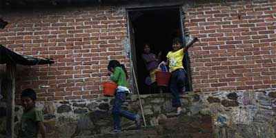 Children carry buckets filled with cornmeal to make tortillas while leaving the house of a neighbor in San Simon Zahuatlan July 13, 2012. Nearly 90 percent of people in this ramshackle settlement live |  Photo: REUTERS/Claudia Daut