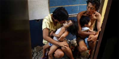Yolanda and Noel sit in the alley outside their shack with two of their children. They scramble each day to get the money to feed the family. Although she is a Roman Catholic, Yolanda disagrees with the church's opposition to contraception and is part of a lawsuit challenging the city ban on providing birth control at public clinics. | Photo: Rick Loomis / Los Angeles Times