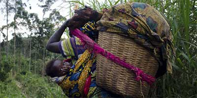 A woman carries her baby as she leaves the village of Ngululu, 80 km north west of Goma