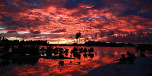 Villagers watch the sunset over a small lagoon near the village of Tangintebu on South Tarawa in the central Pacific island nation of Kiribati. | REUTERS/David Gray