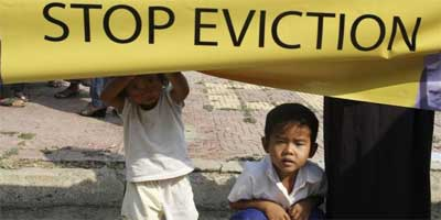 A Cambodian girl holds a banner next to a boy as former residents of the Dey Krahorm community gather in front of the site where they used to live before being evicted by government forces in Phnom Penh January 24, 2012. | Photo: Reuters